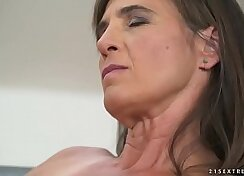 Busty mature in a leatherbike riding her lover dick